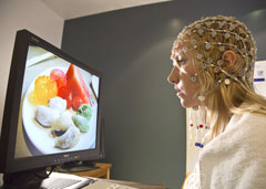 Woman wearing electrodes looks at pictures of food